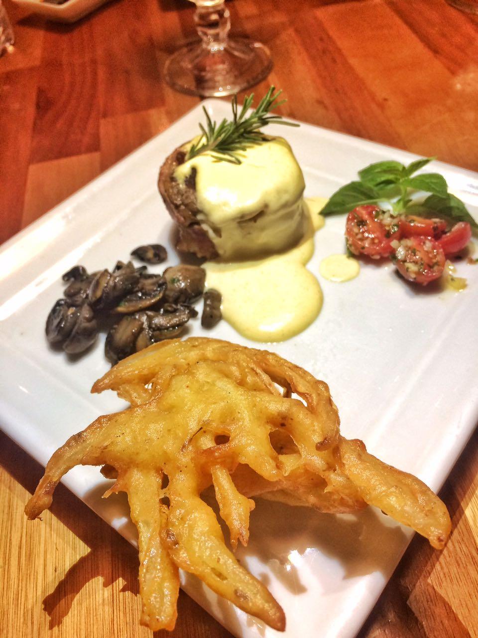 Medalhão de filé mignon com molho de mostarda djon, esculturas de cebola, cogumelos paris e confit de tomate cereja.